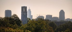 Downtown Raleigh skyline rises up behind the Memorial Belltower.