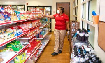 woman in mask walking in food pantry